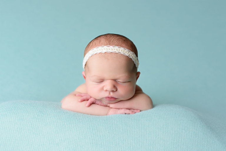 Maternity Newborn Baby Child and Family Photography Near Me beautiful baby girl on teal background wearing white headband by Evan Pollock Professional Photographer at Magnolia Moments photography in her newborn studio