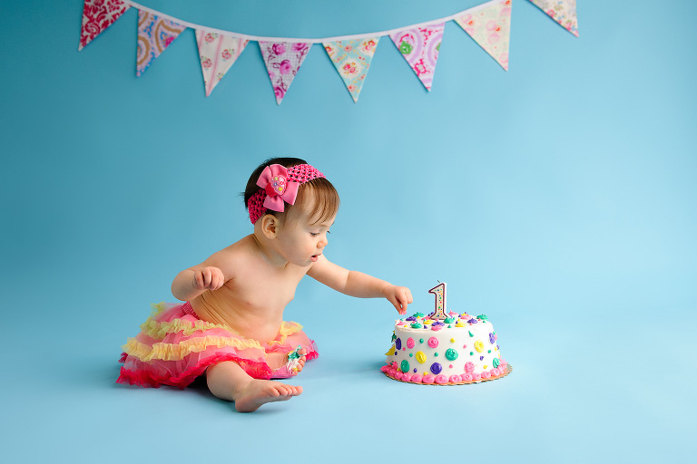 Evan Pollock professional photo of baby in multicolored tutu during a professional photo smash cake photography shoot at a studio near men