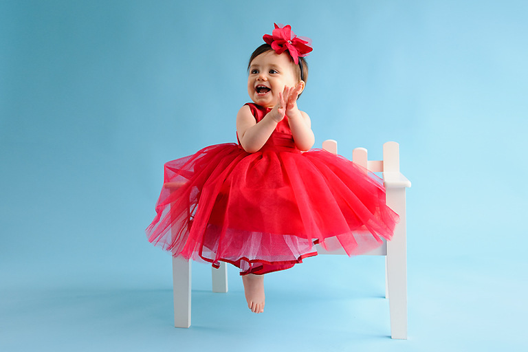 Magnolia Moments Photography professional photo of child wearing a red party dress sitting on bench in the photography studio near me by Evan Pollock Professional Photographer
